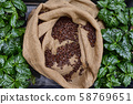 Open bag with coffee beans slices of green leaves. beautiful light, vigor of coffee beans, among 58769651