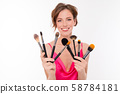 blogger girl with makeup brushes on white isolated background 58784181