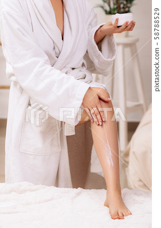 woman applying body cream on her legs 58788529