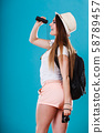 Tourist woman looking through binoculars on blue 58789457