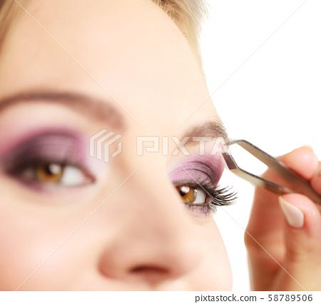 Woman tweezing eyebrows plucking with tweezers 58789506