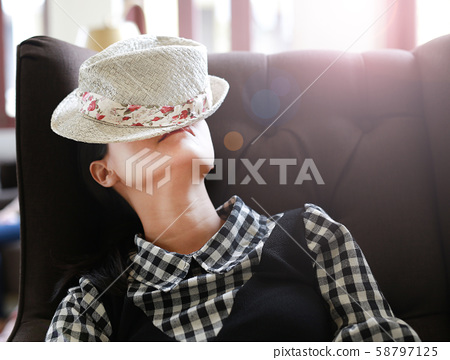Young asian woman sleeping with hat on face in the 58797125