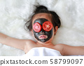 Kid girl in coal peeling face mask with tomato, 58799097