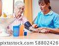 Nurse measuring blood pressure on senior woman 58802426