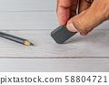 Eraser and error concept, Hand with black eraser 58804721