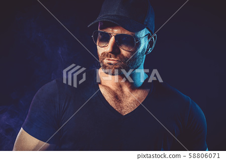 Portrait of brutal bearded man in sunglasses at dark photo studio. 58806071