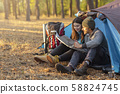 Romantic couple camping outdoors, sitting in tent and checking map 58824745