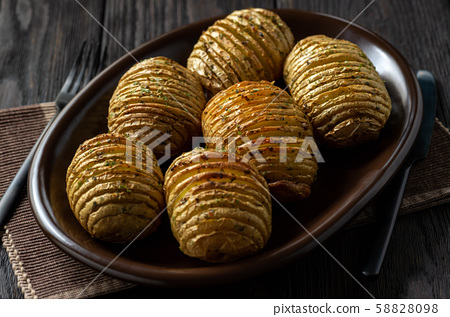 Hasselback potatoes baked with garlic and herbs  58828098