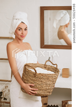 woman holding wicker basket with laundry 58828498