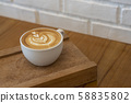 Hot coffee latte art on vintage wooden background 58835802