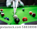 Man's hand and Cue arm playing snooker game or 58838998