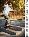 Man in skatepark rides skateboard on warm autumn day 58842678