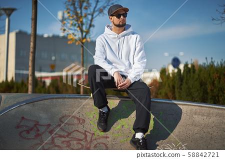 Man in skatepark with skateboard on warm autumn day 58842721