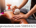 Masseur doing back massage with compress in spa 58856323