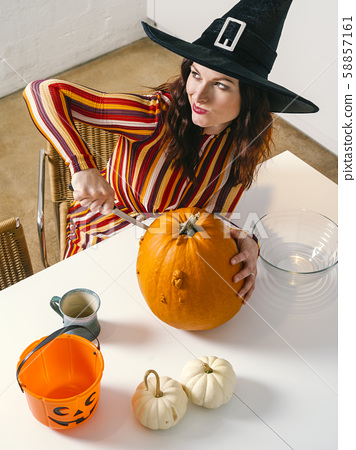 Redhead woman cutting a pumpkin for Halloween 58857161