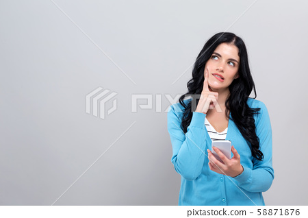 Young woman with smart phone thinking about something 58871876