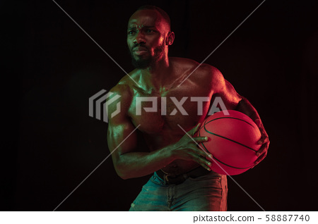 Young african-american basketball player against dark background 58887740