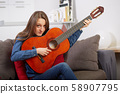woman play guitar at home 58907795