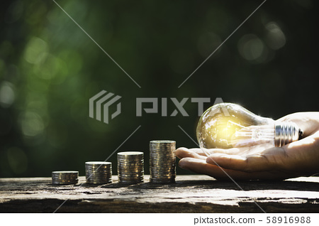 Hand of male holding a light bulb with stack of 58916988