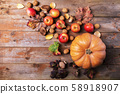 Orange pumpkin with cardoncelli mushrooms, apples, walnuts and colorful leaves on old rustic wooden boards. Autumn Thanksgiving day background. Beauty harvest autumn concept.  58918907