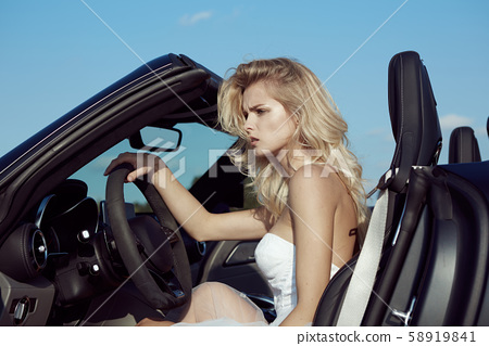 Fashion portrait of dreamy woman in the luxury car. Girl wearing blue dress. No retouch 58919841