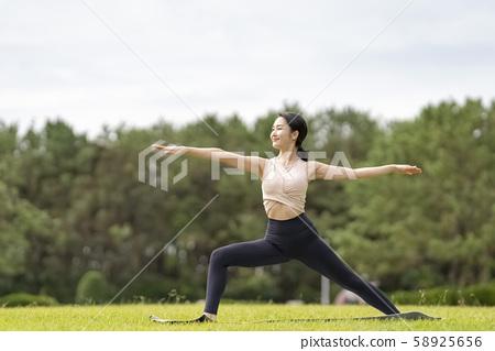 요가 잔디 공원에서 휴식 해방감 (영웅의 포즈 전사 포즈) 엉덩이의 탄력과 균형 감각, 집중력 58925656