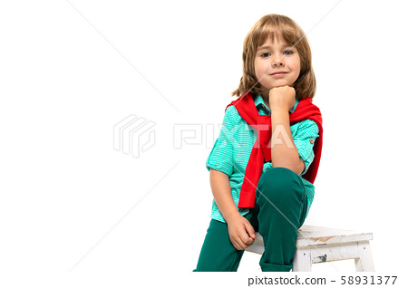 Little caucasian boy sits on a chair with red sweatshot around his neck propped up a fist the head 58931377