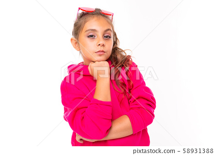 Portrait of a fashionable girl in pink sweatshirt, pink sunglasses is thinks about something 58931388
