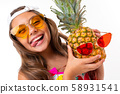 A little girl with long crucified hair in sunglasses and swimsuit is played with pineapple in 58931541
