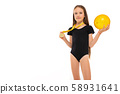 Picture of a gymnast girl in white short socks and black trico full height stands with yellow ball 58931641