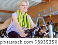 Senior woman on an exercise bike in the gym 58935350