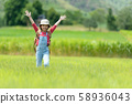 Asian girl raise arms and jumping on the green  58936043