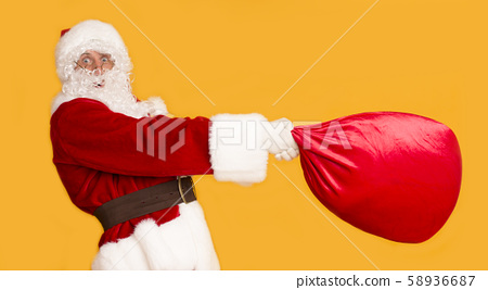 Funny Santa trying to pick up big bag full of presents on orange 58936687