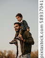 Father giving son ride on his shoulders during walking in autumn park. 58937041
