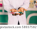 Hands of African American man pharmacist holding tablets and pills, while standing in modern 58937582