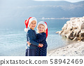 Happy smiling kids in Santa hats at Christmas. Little girls are hugging and laughing on sea beach 58942469