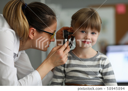 Pediatrician examines ear of sick child in office 58945894