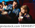 Young caucasian family watching a film at a movie theater 58946857