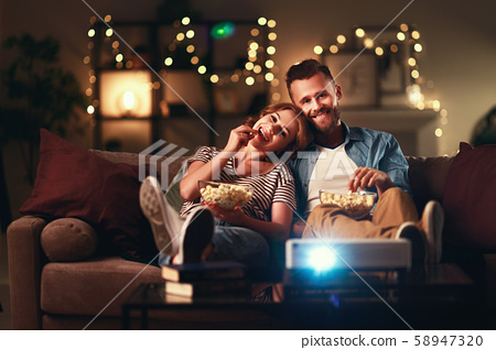 Family couple watching television projector at 58947320