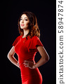 Young beautiful woman wearing a red dress on the dark background 58947874