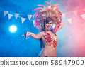 Cabaret, dancer and holidays concept - Cute young girl in bright colorful carnival costume on dark 58947909