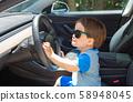 Toddler boy playing in a car 58948045