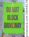Do Not Block Driveway sign on a mesh wire fence 58948579