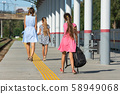 A girl and a daughter walk along the platform of 58949068