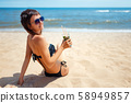 Woman holding glass of fresh mojito cocktail on the beach 58949857