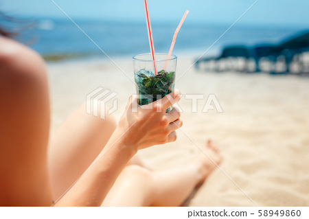 Woman holding glass of fresh mojito cocktail on the beach 58949860