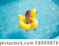 Funny little girl swims in a pool in an yellow life preserver 58949878
