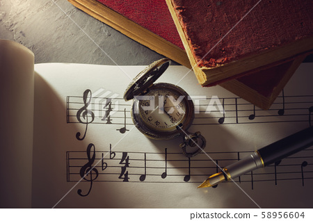 Music notes and old book with pocket watch on wooden table background in morning light. Writing chords by vintage pen. Closeup and copy space for text. Concept of Music lovers. 58956604