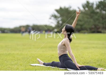 瑜伽在草公園裡放鬆的感覺美麗的女人,像藝術體操一樣柔軟的身體 58975469