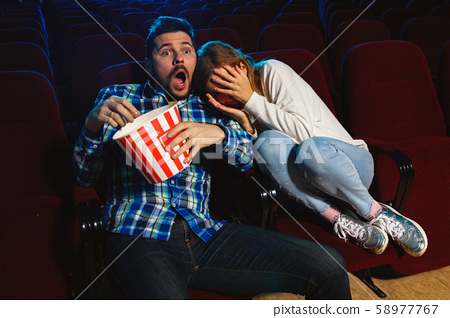 Attractive young caucasian couple watching a film at a movie theater 58977767